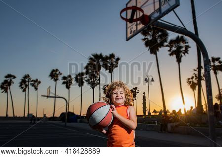 Portrait Of Kid Basketball Player. Child Hold Basketball Ball On Venice Beach Basketball Court.