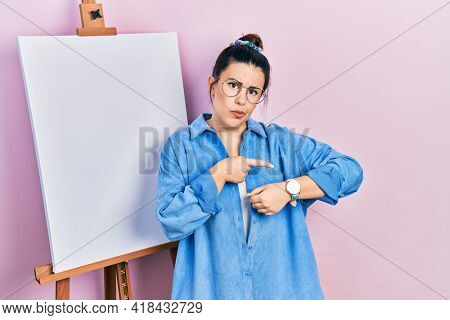 Young hispanic woman standing by painter easel stand in hurry pointing to watch time, impatience, upset and angry for deadline delay