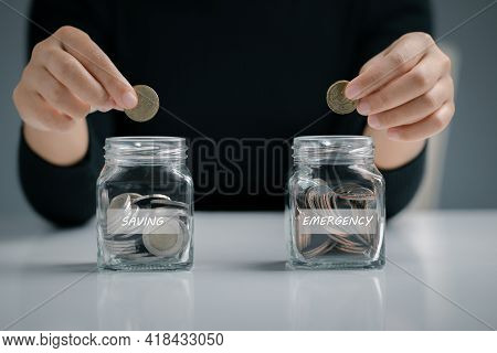 Woman Hand Putting Coin In The Glass Jar For Saving And Emergency, Saving For Emergency Concept.