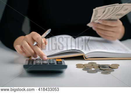 Woman Using Calculator With Pen In Her Hand And Hold Dollar Bill For Calculating Financial Expense A