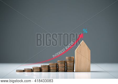 Text Interest Rate And Percent Symbol On Red Arrow Moving Up With Wooden House And  Stack Of Coins,