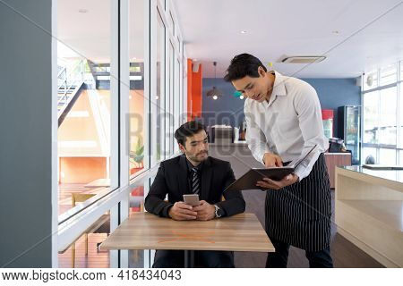 Young Businessman In Suit Listening To The Waiter While Holding Mobile Phone. Asian Waiter In Apron