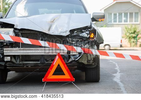 Red Emergency Stop Triangle Sign And Red Warning Police Tape Afore. Destroyed Car In Car Crash Traff