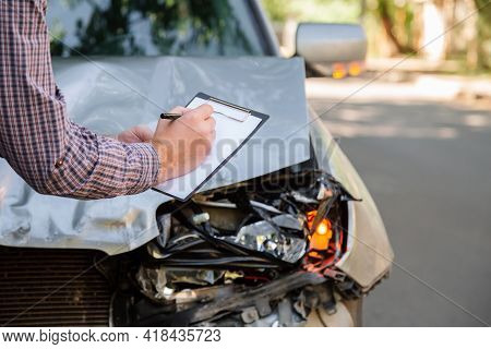 Male Insurance Agent With Auto Insurance Blank Against Destroyed Car In Car Crash Traffic Accident O