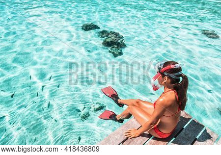 Travel Vacation Snorkeling. Snorkel swim woman going snorkeling in coral reefs for tropical water fun at resort with snorkelling mask, fins
