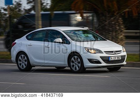 Alanya, Turkey  - April 13  2021: White Opel Astra   Is Driving Fast On The Street On A Warm Summer