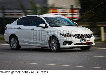 Alanya, Turkey  - April 13  2021:  White Fiat Albea Is Driving Fast On The Street On A Warm Summer D