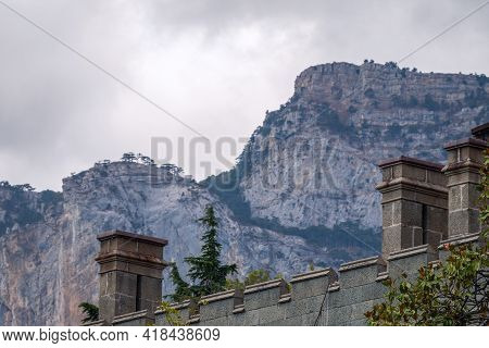 The Walls And Towers Of The Old Palace On The Background Of High Mountains And Cloudy Sky
