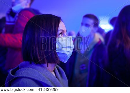 Girl In Face Protective Mask At Concert On Background Of People Crowd