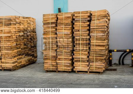 Wooden Display Crates Stacked Neatly Beside Industrial Building.