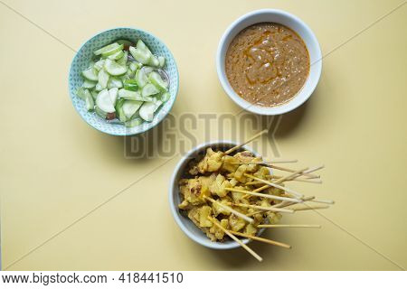 Grill Pork Satay Served With Bean Sauce And Pickle Cucumbers And Onions In Vinegar. Thai Street Food