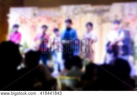 Abstract Blurred Background Of Master Of Ceremonies On Stage At Wedding Ceremony In Convention Hall