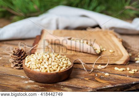 A Round Plate With Pine Nuts, A Scoop For Loose Products On A Wooden Table, A Pine Cone. The Fabric