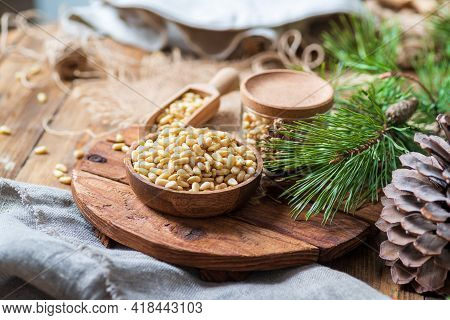 Pine Nuts, Pine Cone, A Branch On A Cutting Board, Linen Cloths Nearby. Everything Is On The Table,