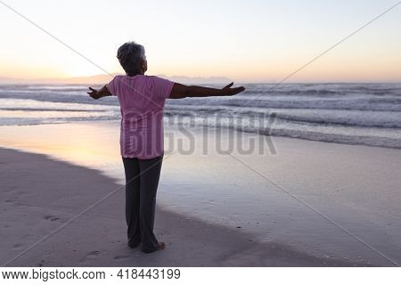 Rear view of senior african american woman standing with her arms wide open at the beach. travel vacation retirement lifestyle concept