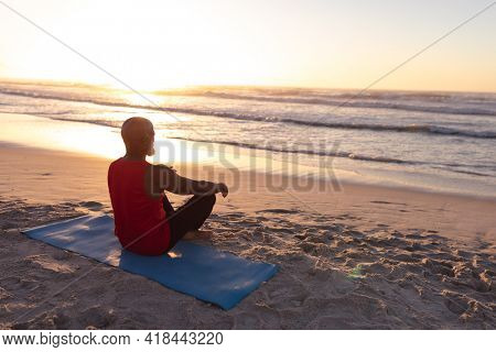 Senior african american man meditating and practicing yoga while sitting on yoga mat at the beach. fitness yoga and healthy lifestyle concept