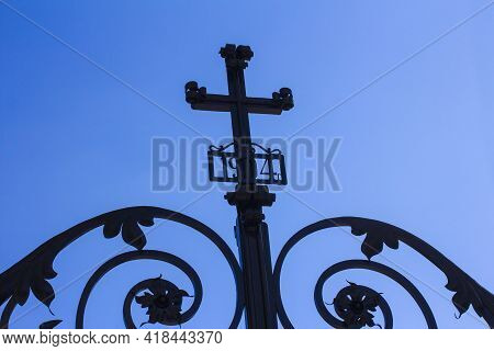 Forged Gate With A Cross At The Entrance To The Cathedral Against The Blue Sky. Forged Date 1904.