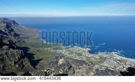 South African Coastline From Above. Blue Atlantic Ocean, Foam Of Waves, Sky, Uneven Banks, City Hous