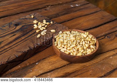 A Wooden Cutting Board, On Which Peeled Pine Nuts Are Poured, Next To A Bowl Of Nuts. Background Fro