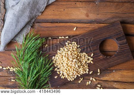 Pine Nuts Are Heaped On A Cutting Board. On The Table Next To It Is A Pine Branch With Green Needles