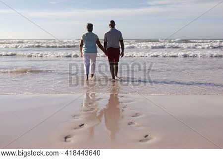 Rear view of senior african american couple holding hands while walking on the beach. travel vacation retirement lifestyle concept