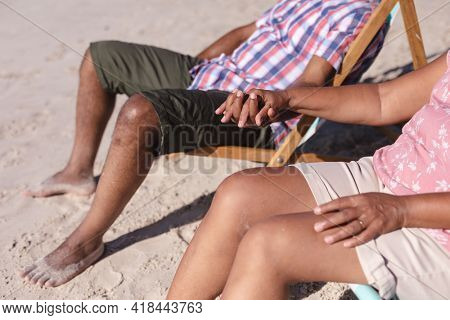 Mid section of senior african american couple holding hands while sitting on deck chairs at the beach. travel vacation retirement lifestyle concept