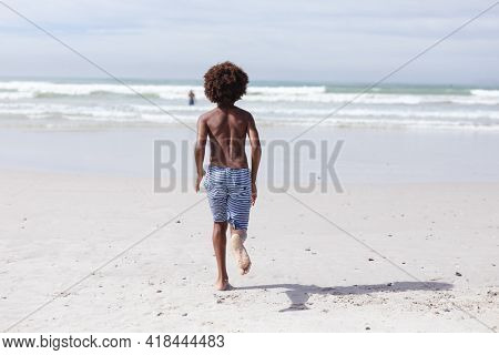 Rear view of african american boy running on the beach. travel vacation summer beach concept