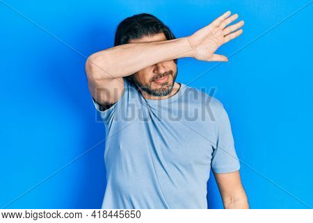 Middle age caucasian man wearing casual clothes covering eyes with arm, looking serious and sad. sightless, hiding and rejection concept