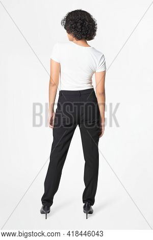 Woman in black slack pants and white tee rear view
