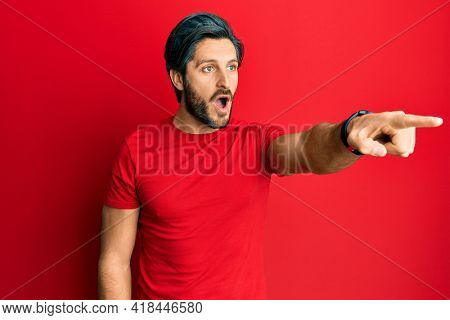 Young hispanic man wearing casual red t shirt pointing with finger surprised ahead, open mouth amazed expression, something on the front