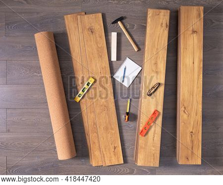 Laminate floor on wood background texture and tools. Wooden laminate floor plank with copy space