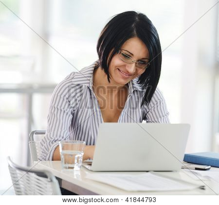 Portrait of a pretty female student working on laptop inside university building