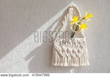 Handmade Macrame Bag With Flowers On The Light Wall. Eco Friendly Natural Macrame Cotton Bag. Hobby