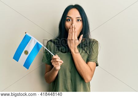 Young hispanic girl holding argentina flag covering mouth with hand, shocked and afraid for mistake. surprised expression