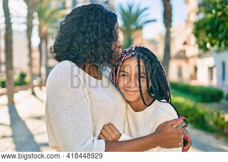 Beautiful african american mother and daughter kissing and hugging. Standing with smile on face standing at the park.