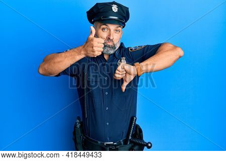 Middle age handsome man wearing police uniform doing thumbs up and down, disagreement and agreement expression. crazy conflict