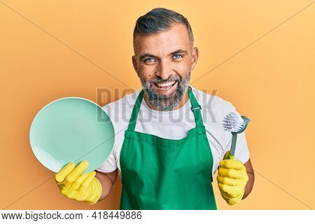 Middle age handsome man wearing apron holding scourer washing dishes smiling and laughing hard out loud because funny crazy joke.