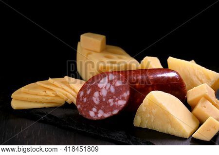 Several Types Of Yellow Cheese In Chunks And Cut Into Slices And Piece Of Sausage Loaf On Black Ston
