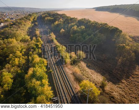 Railroad and train in autumn forest in foggy sunrise. Top Aerial view rural railway