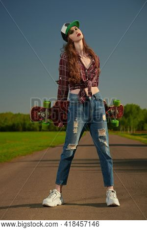 Cool modern teen girl poses with longboard on a highway outside the city. The spirit freedom and autumn adventures.