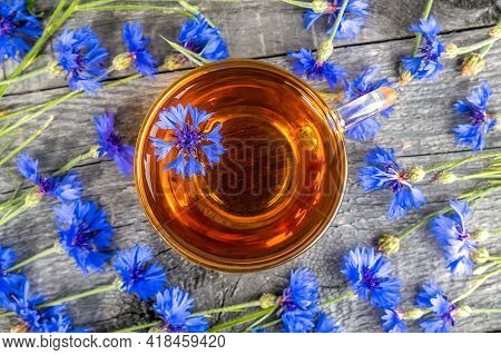 Cup Of Herbal Tea And Blue Cornflowers Flowers On Wood Background. Top View Flat Lay Copy Space.