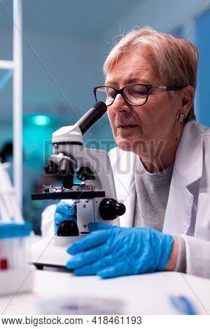 Experienced Scientist Engineering Healthcare Blood Sample Using Microscope