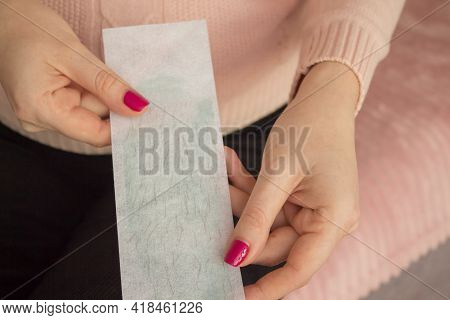 Hair Removal Wax Strips With Hair Close-up In The Hands Of A Young Woman. Body Hair Removal Concept
