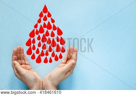 Baby's Hands Catch Drops Of Blood And On A Blue Background, World Blood Donor Day, Charity And Care,