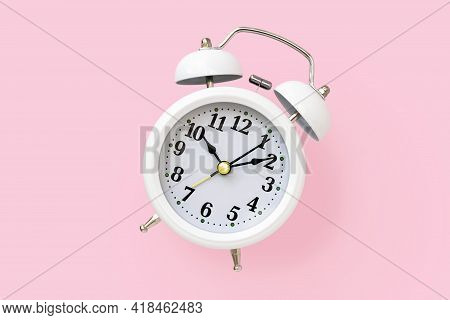 White Metal Retro Alarm Clock With A Round Dial On A Pink Background, Top View. Minimalistic Design.