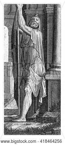 The apostle Matthew standing by a column in a room. He is leaning on a long staff with both hands.