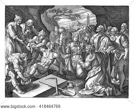 Lazarus, who has just come out of his grave alive, is detached from the grave cloths by his family.