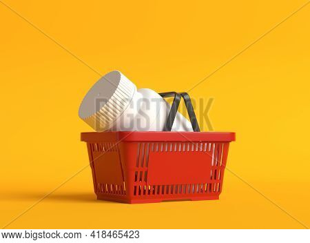 White Pill Bottle In A Red Plastic Shopping Basket On Yellow Background With Copy Space. Medicine Co