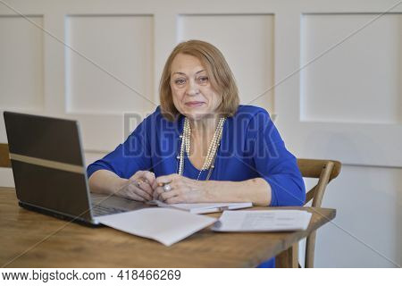 Senior Woman Sitting At Desk Using Laptop Computer, Looking At Screen. The Concept Of Senior Employm