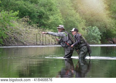 fishing guide with a young woman fly fishing for trout in a clear river